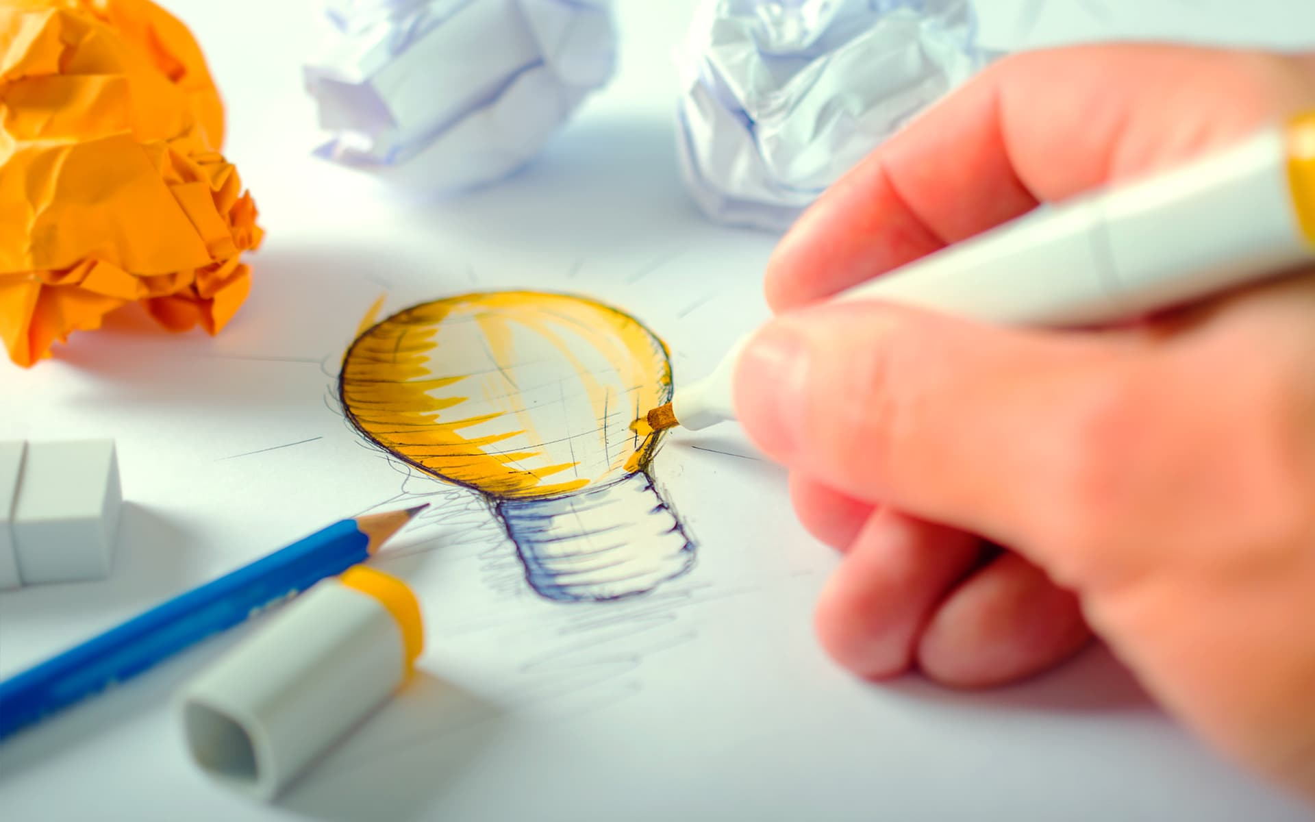 The picture shows a hand drawing a light on a sheet of paper symbolizing a new innovation