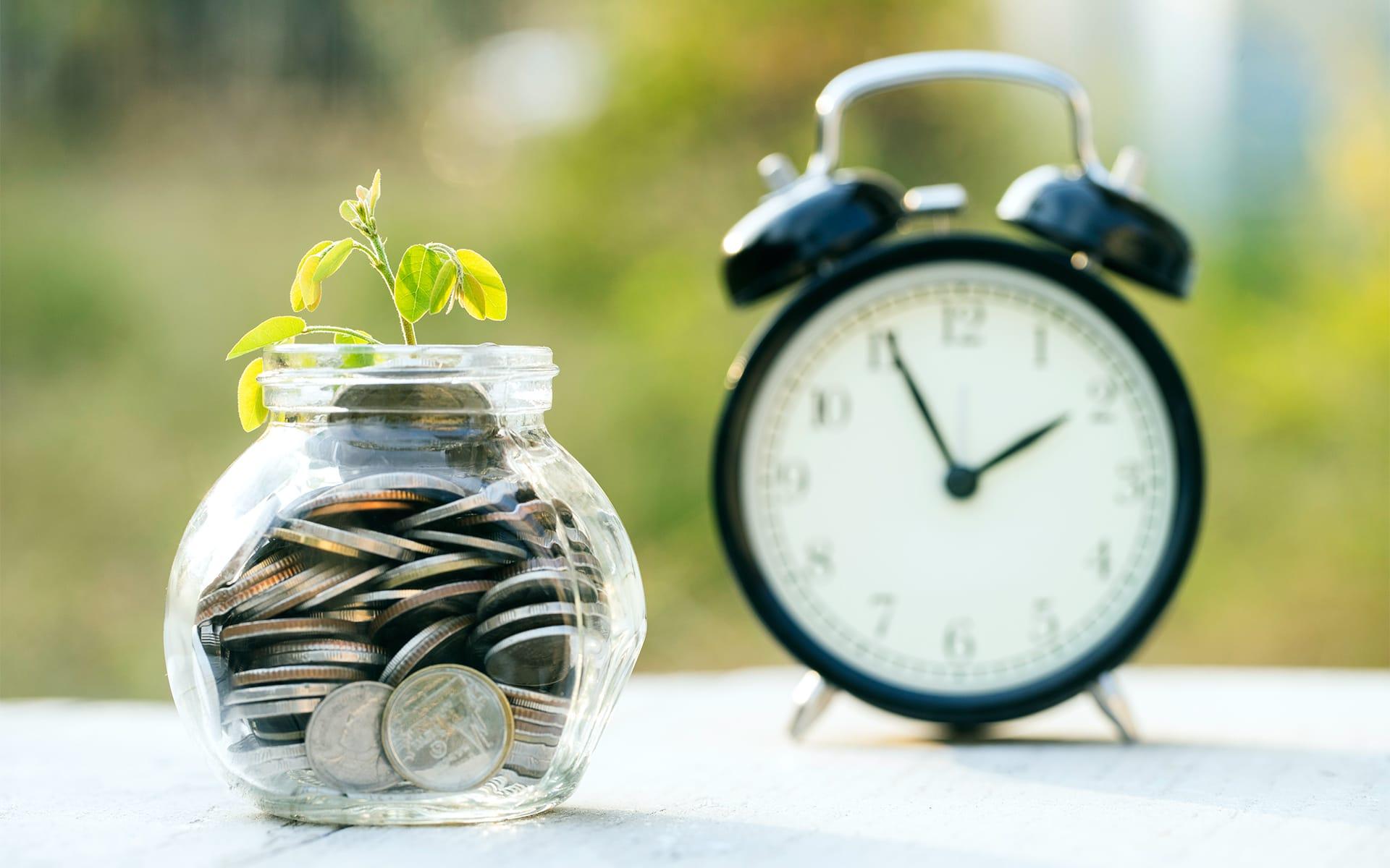 Zeit und Kosten sparen mit Aufgabenmanagement: Wecker und Glas mit Münzen