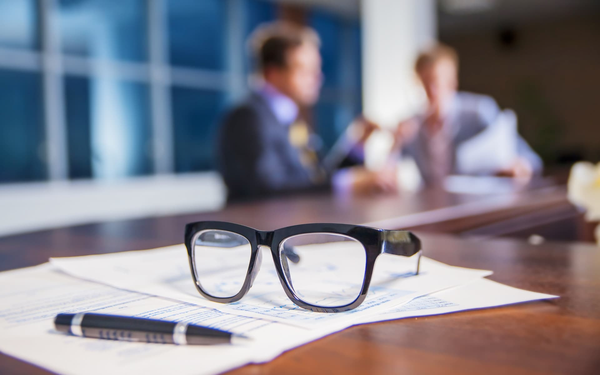 Process Thinking European Insurance - Glasses laying on a table, people talking in the background