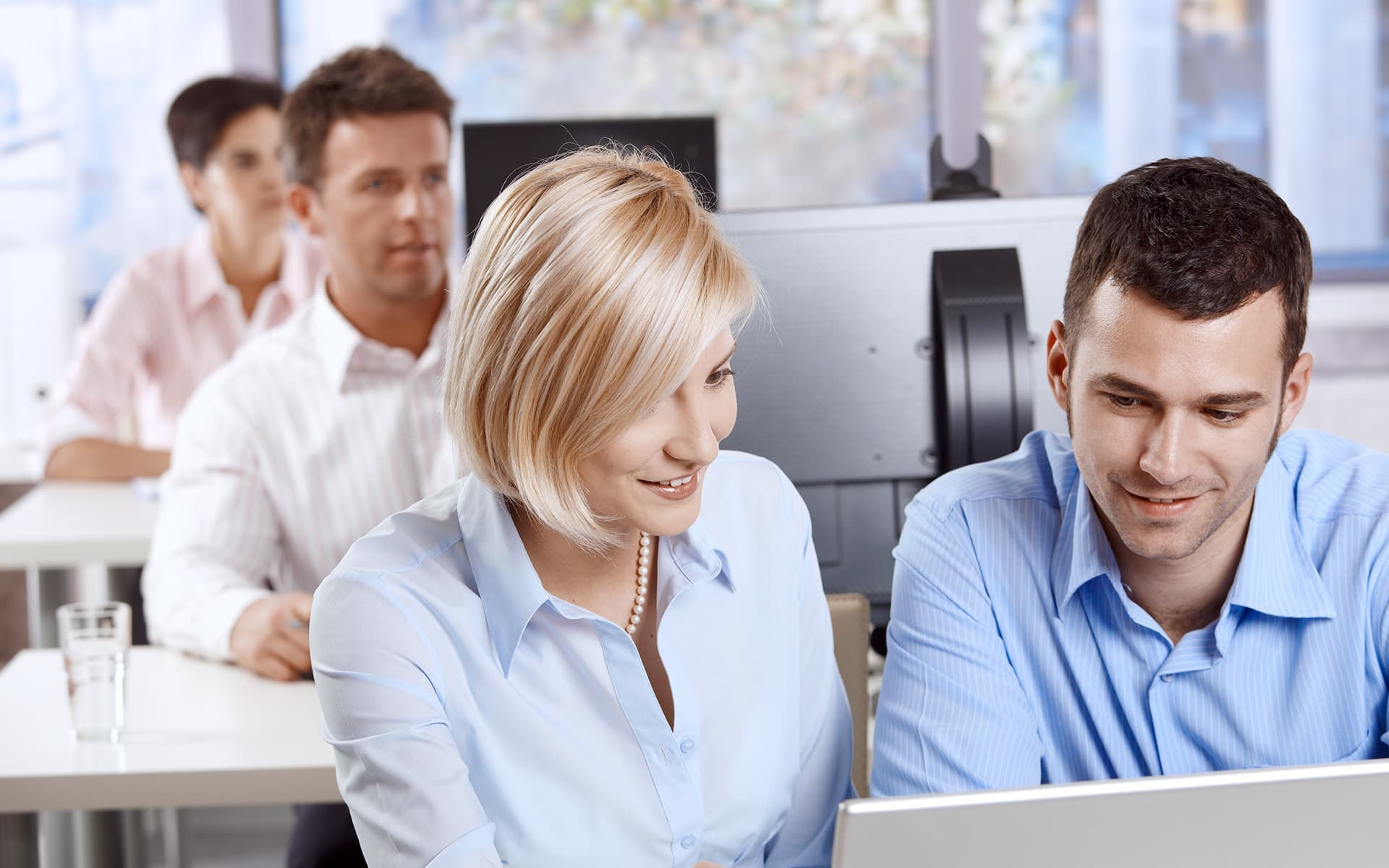 How to automate your training course workflow - 2 employees sitting iin front of a computer