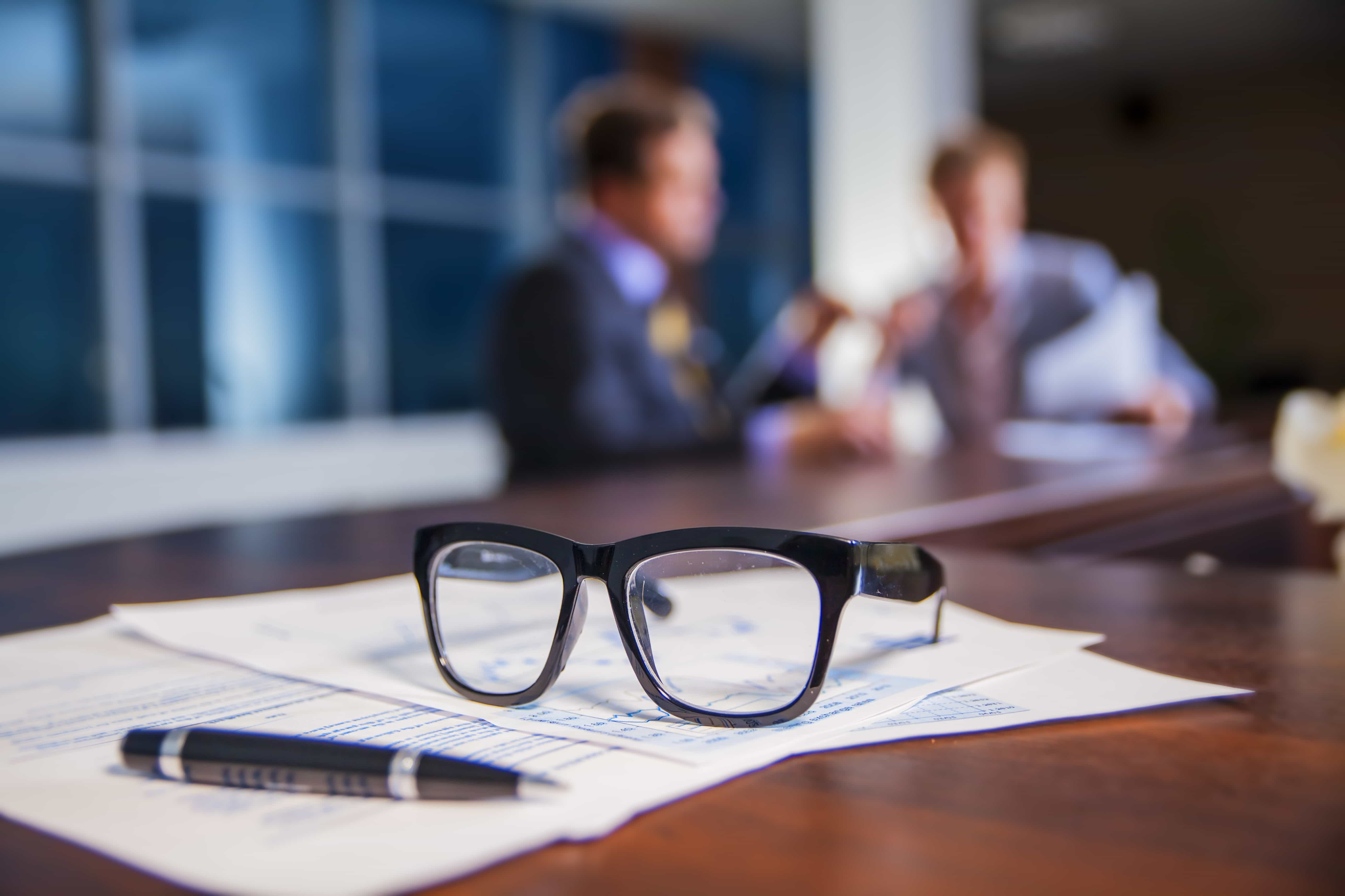regulatory compliance: Glasses laying on a table, people discussing in the background
