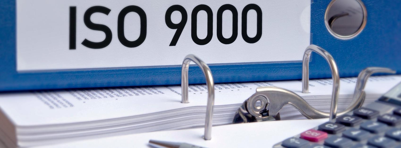 ISO-9000-Webinar: Blauer ISO-Ordner, der auf einem Tisch liegt