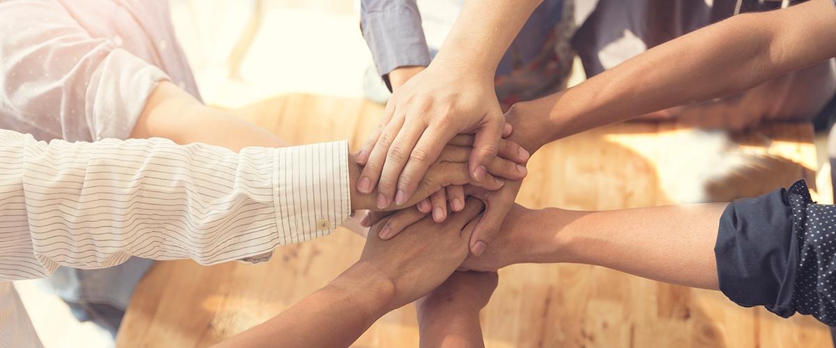 BPM und Business Transformation - Viele Hände übereinander als Zeichen von Teamwork