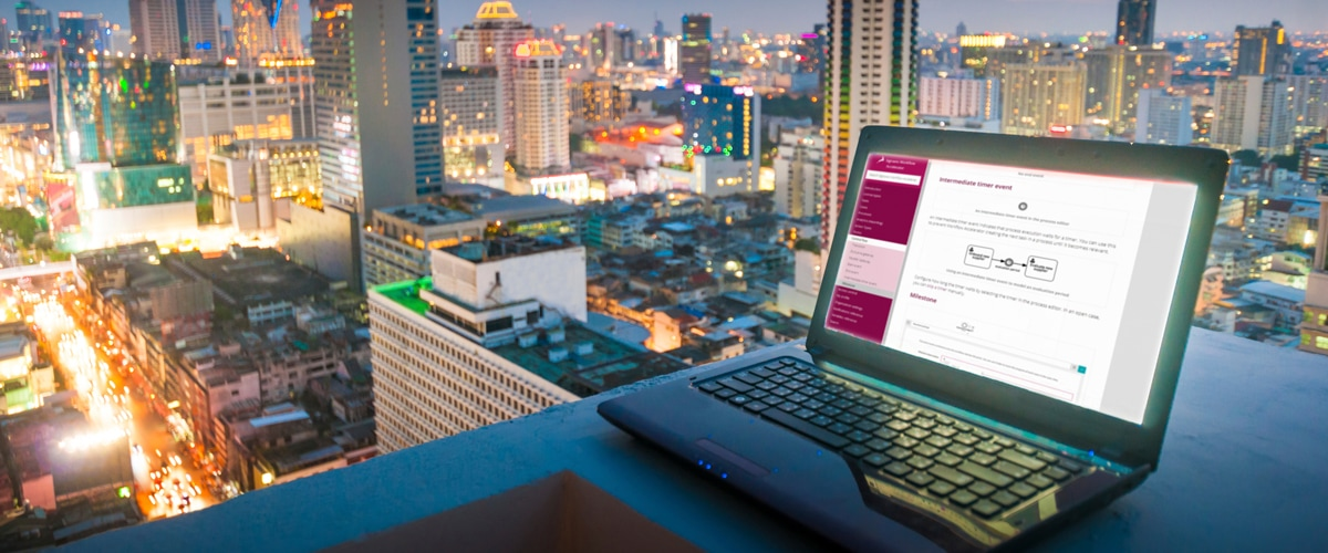 process milestone model on laptop screen with skyline in the bacjkground