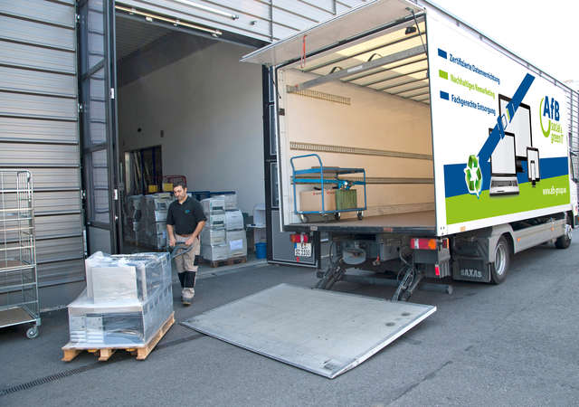 Pallets of laptops being loaded into a truck