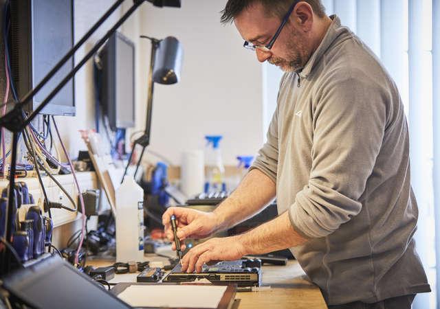 Man fixing a donated laptop